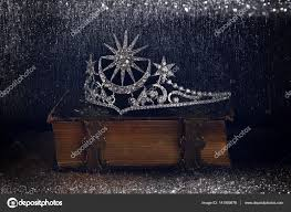 low key image of beautiful diamond queen crown on old book vine filtered with glitter overlay selective focus meval period concept photo by