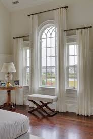 how to hang curtains for an arched window see more these staggered sheers are a great way to draw attention to the architectural interest of the