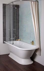 white resin free standing tub with shower curtain and glass board panel on natural polished walnut