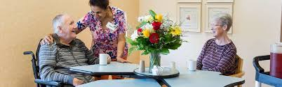 sunnyside home staff laughing with resident in dining room