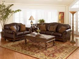 charming antique rug under coffee table blended with luxurious brown leather sofa and refreshing potted plant