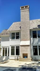 white brick chimney w two fireplaces indoor and outdoor
