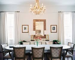 upholstered dining chairs surrounding an oval table and a crystal chandelier overhead chandelier lights for