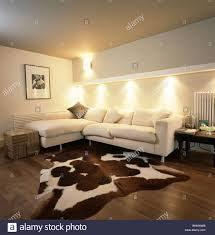 Living Room With Corner Sofa Artificial Cowhide Rug In Modern Living Room With Down Lighting