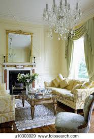 cream brocade sofas and glass topped coffee table in cream panelled drawing room with glass chandelier