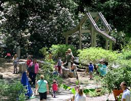 children and pas engage in activities in the hollow at heritage museum gardens