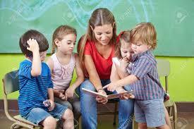 Nursery Teacher Children And Nursery Teacher Reading Book Together In Kindergarten