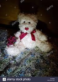 Teddy Bear Mit Rose Bouquet Auf Dem Bett Zu Hause Stockfoto