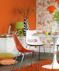 awesome dining room with orange wall paint white orange chairs white round table with orange rug image