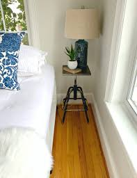 diy nightstand next to bed with blue lamp book and plant on top