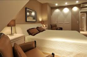 twin wall light on wooden wall small basement bedroom ideas unique cream color lounge chair white black patterned bed grey paint wall laminate wooden floor basement bedroom lighting ideas