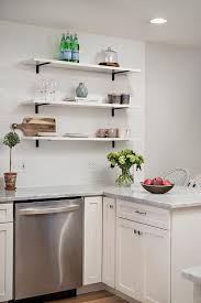 stacked white marble kitchen shelves accented with iron brackets stand over a marble top kitchen peninsula lined with french bistro barstools
