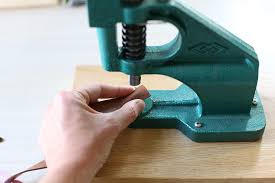 align holes and push the rivet post through layers from exterior of bag to the interior you can probably do it the opposite way as well working from the
