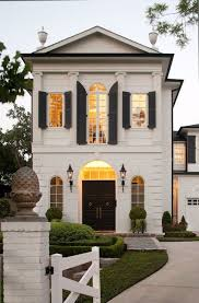 exterior paint colors for colonial style house. french home exterior with greek columns and black shutters. front entrance door arched windows iron lanterns flanking grand entrance. paint colors for colonial style house