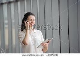 young businesswoman talking on mobile phone while standing by window in office beautiful young female beautiful bright office