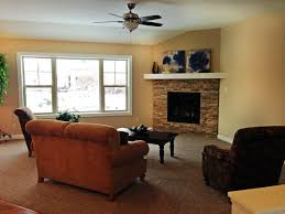 corner gas fireplace with cozy sofa and ceiling