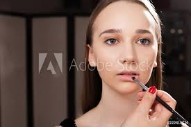 fotografía makeup artist applying a lip gloss on lips of a young pretty europosters es