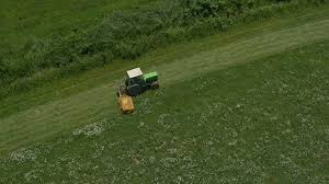 grass field aerial. AERIAL: Tractor Mowing In A Big Grass Field Stock Video Footage - Videoblocks Aerial D