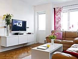 Living Room : A White Table With Glasses And Vases Of Flowers On Top Of It  Plus A Book Then A Sofa With Pillows And A Television And A Vase Of Flowers  ...