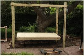 hanging bed platform being added to wooden frame outdoors