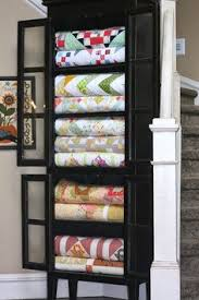 Quilts beautifully displayed in a black cabinet, posted at A ...