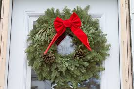 hang wreaths on the inside or outside of glass doors from inside wreaths on glass are backlit by natural light and serve as an ornamental foreground to
