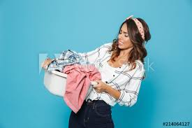 portrait of dissatisfied young woman 20s carrying laundry basket with dirty clothing isolated over blue