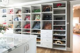 walk in closet with open shelving lined with designer bags