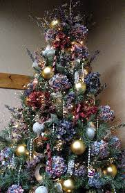 this tree has two kinds of gold sparkle ribbon twisted through huge balls silver beaded apples and a few little foilwrapped gift packages beads on christmas e87