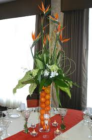 Tropical Birds of Paradise highlight this spectacular centerpiece on a  glass riser filled with navel oranges