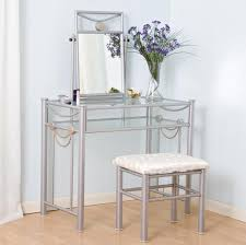 vintage glass makeup vanity table featuring detailed iron framed plus glass shelf and glass top with adjule table mirror