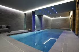 ... Grey walls and recessed lighting give this indoor pool a minimalist  appeal