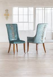 our kingsley dining chairs covered in como silk velvet teal and shown with zola embroidery