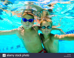 Kids swimming underwater in pool enjoying the relaxation of summer