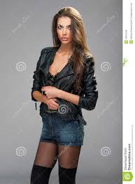 beautiful brunette woman fashion model wearing black leather coat and jeans