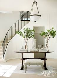 an globe pendant from circa lighting hangs over the entry table in the foyer