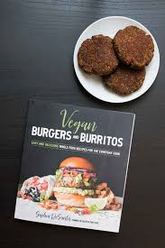 an overhead photograph of the vegan burgers burritos cookbook there s a side plate with