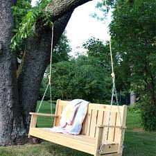a hanging bench with a quilt on it
