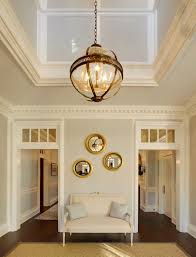 incredible two story foyer illuminated by a restoration hardware victorian hotel pendant over gray walls finished with dentil crown molding above doorways