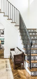 The stair tiles are beautiful with the wooden steps and metal banister.