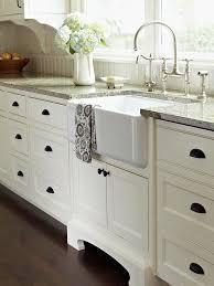 white kitchen cabinets with bronze farmhouse sink