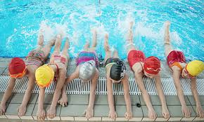 children splashing in a swimming lesson