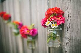 hanging jar flowers on outdoor backyard wooden fence for decoration ideas