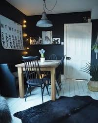 dark coloured dining room painted in farrow and ball off black with oak dining table ercol chairs and cowhide rug over white painted floorboards