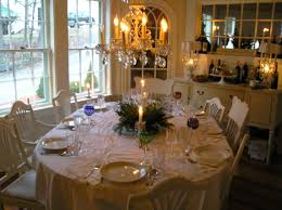 romantic dining table centerpiece with candle sticks plus fresh greenery and traditional crystal chandelier 16