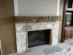 reclaimed wood beam installed as fireplace mantel
