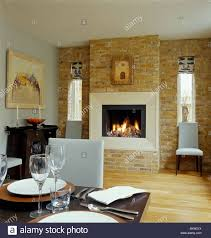 Lighted fire in fireplace in exposed brick wall in modern dining room with  white leather dining chairs and wooden flooring