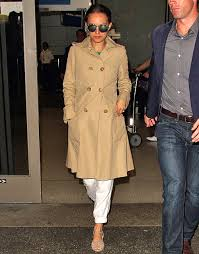 natalie portman covered up her baby p with a beige trench coat as she arrived in los angeles on sept 19 the brunette beauty had been promoting her