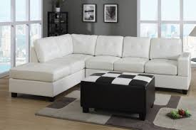 white color modern leather sectional sleeper sofa bed with wooden legs in living room with black leather ottoman table and laminate wooden floor tiles