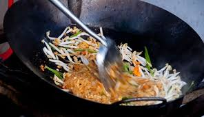 the best thai dishes that you need to try pad thai food in a pan being stirred